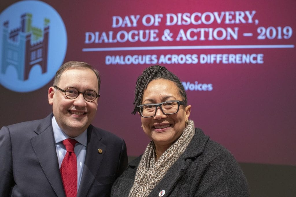 """Andrew D. Martin and Adrienne Davis in front of sign reading """"Day of Discovery, Dialogue & Action - 2019, Dialogues Across Difference"""""""