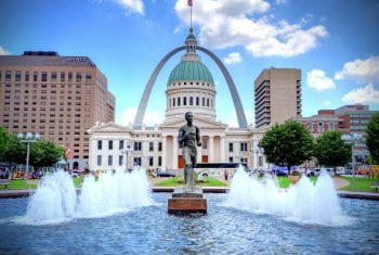 Runner statue with the old courthouse and Arch behind it