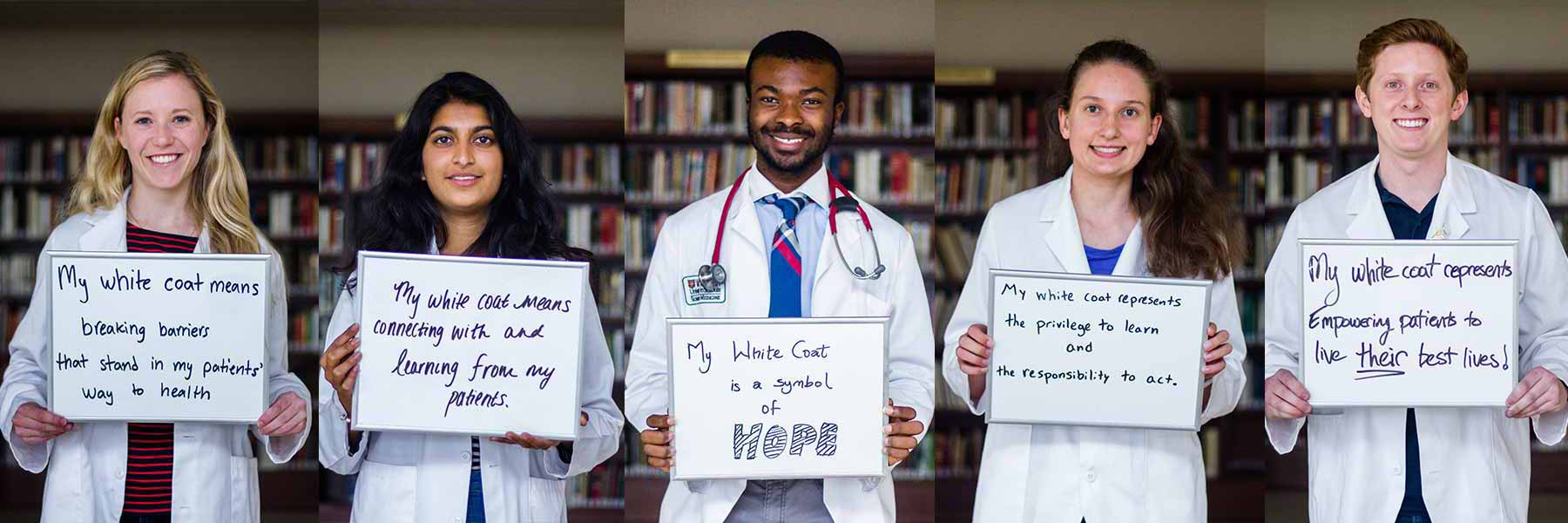 Incoming medical students hold signs stating what their white coat means to them.