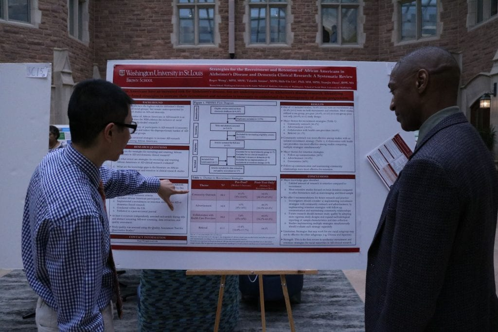 Social Work student Roger Wong explains their research to Dean of the Graduate School, William Tate