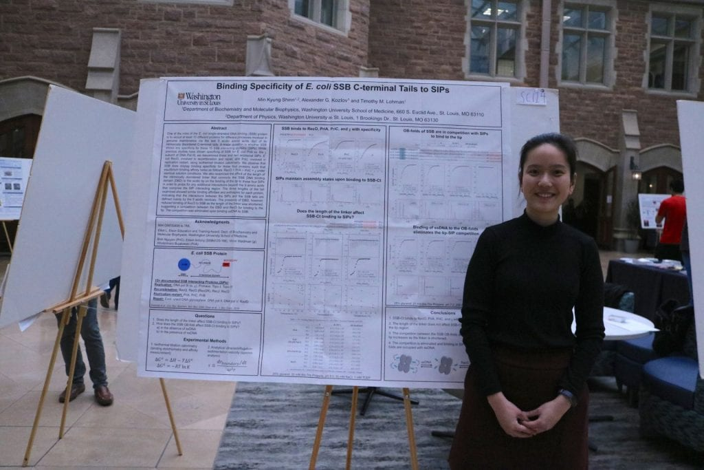 Physics student Min Kyung Shinn poses next to their poster