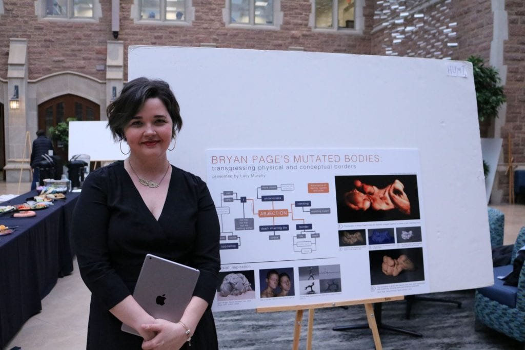 Art History and Archaeology student Lacy Murphy poses with their poster