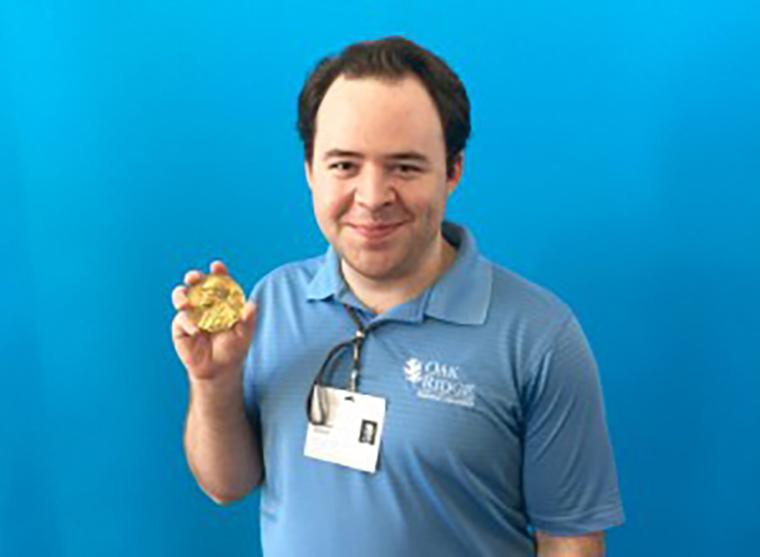 Student Matt Riblett holding a Nobel Prize in Physics medal.