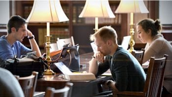 Three students study in a library on WashU campus.