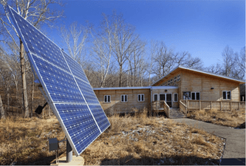 Solar panels in front of the wooden office, lab, and classroom building at the Tyson Research Center, one of the first buildings in the world to achieve Living Building Challenge certification.