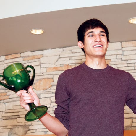 A student holds the green cup trophy, an award for dormitories that conserve the most energy and water