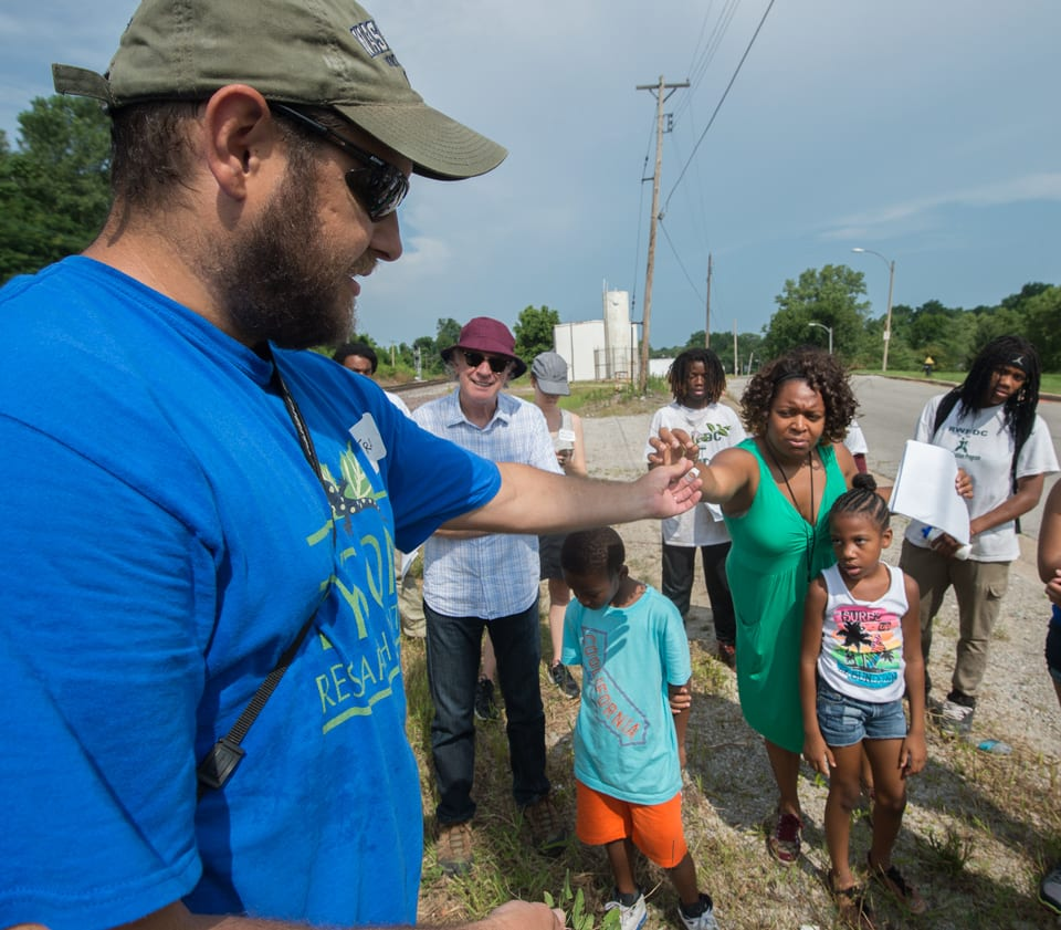 Travis Mohrman, an ecologist at Washington University's Tyson Research Center, talks to residents in a north St. Louis neighborhood about the local ecosystem.