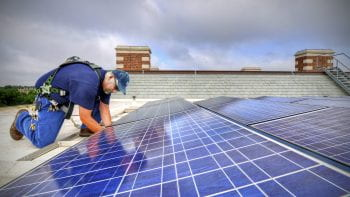July 22, 2013 - Kevin Denzl works on solar panels on the roof of Brauer Hall. Photos by James Byard