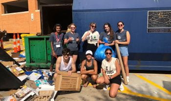 Students pose in front of recycling compacter. They stand amidst trash that has yet to be sorted.