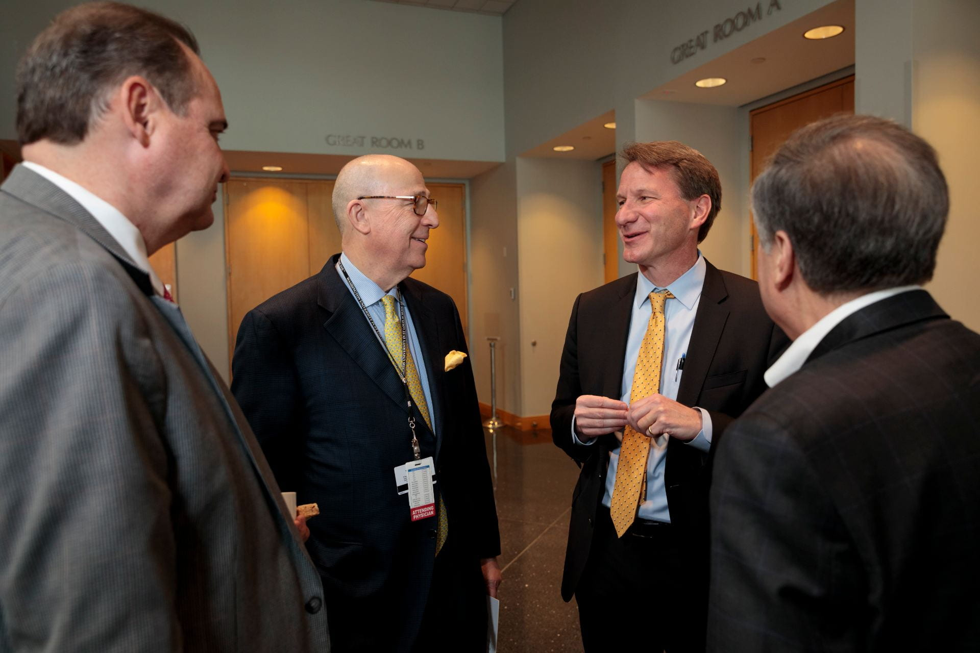 """Dennis Hallahan, MD, Chairman of the Department of Radiation Oncology, left, Timothy Eberlein, MD, Director of Siteman Cancer Center, NCI Director Norman E. """"Ned"""" Sharpless, MD, and Robert Schreiber, PhD, talk during a break."""