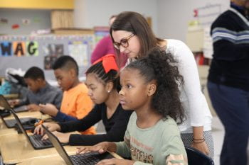 ISP associate director Rachel Ruggirello looks over the shoulder of Barbara C. Jordan Elementary School students as they work on the Hour of Code Stormy Science challenge.