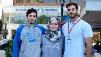 Lab members Omar and Khlaid Saffaf with sister Alaa in front of SLCH