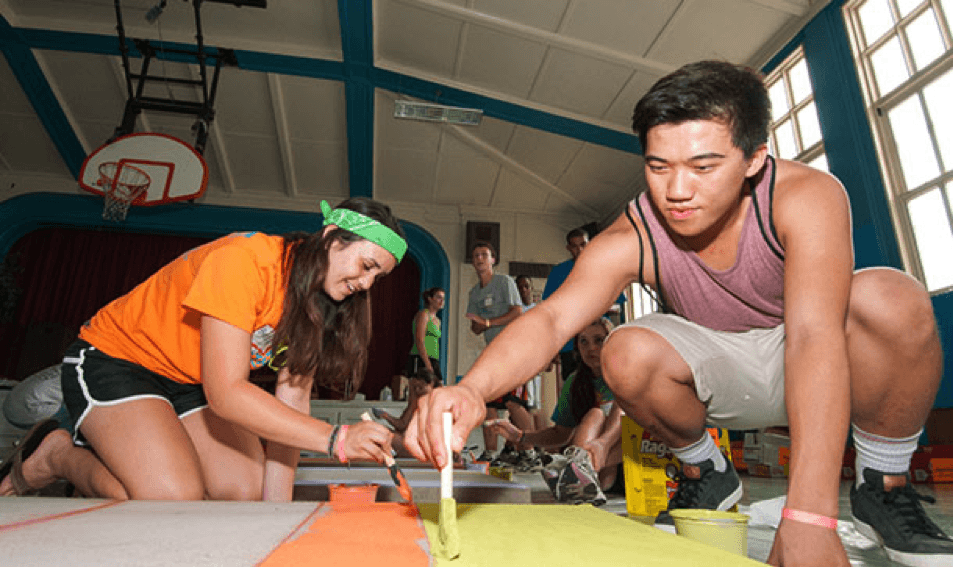 Students paint posters for Service First, a WSWU-funded project.