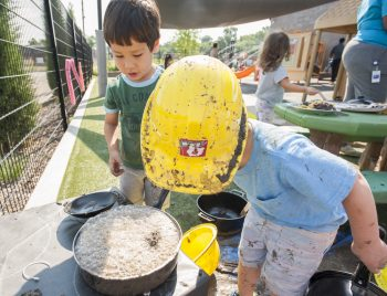 Two small children, one in a yellow hard hat, watch a pot of bubbles.