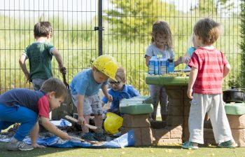 A group of small children , some in yellow hard hats, play in the mud near a playground picnic table