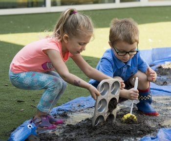 A young boy and girl play in the mud with kitchen untensils.