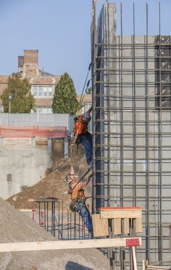 Two construction laborers work together on a scaffold.