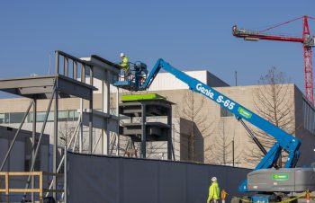 A construction worker in a safety vest accesses the top of a metal structure using a cherry picker and a red crane is in the background.