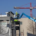 Construction worker in a cherry picker places a top element on a metal structure with a red crane in the background