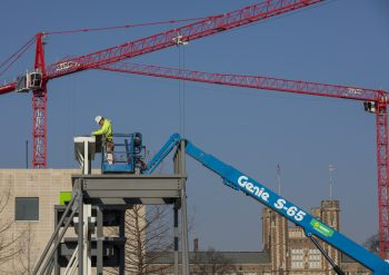 Construction worker in a cherry picker places an element atop a metal structure on the East End construction site at Washington University in St. Louis