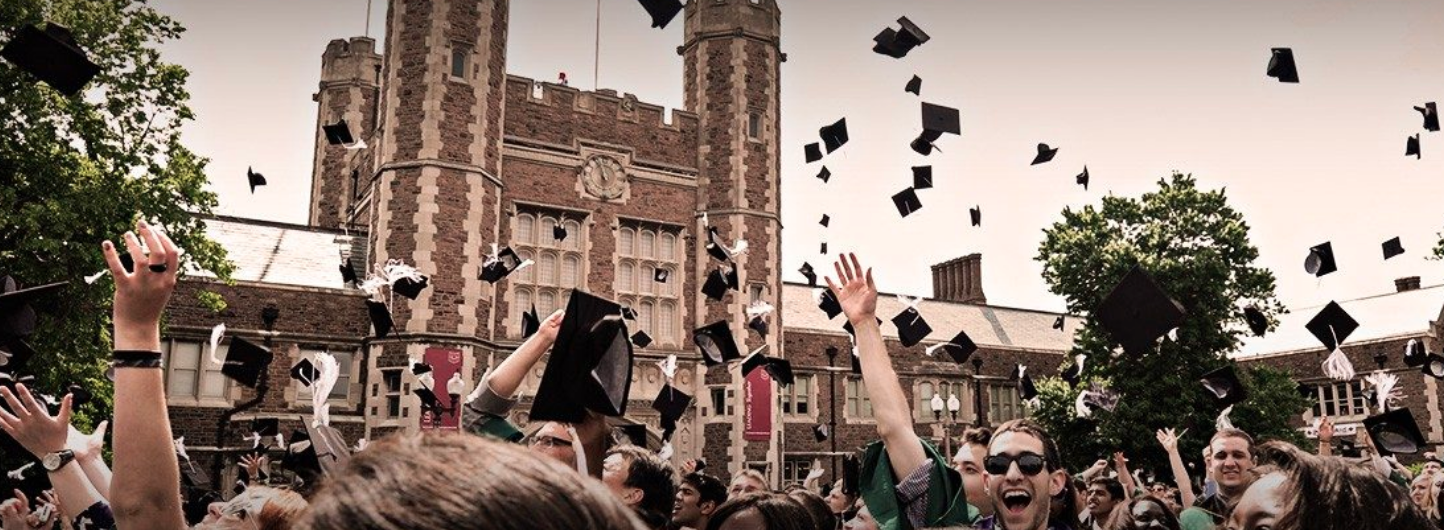 Graduating college students throw their caps at Commencement with a college gothic building in the background
