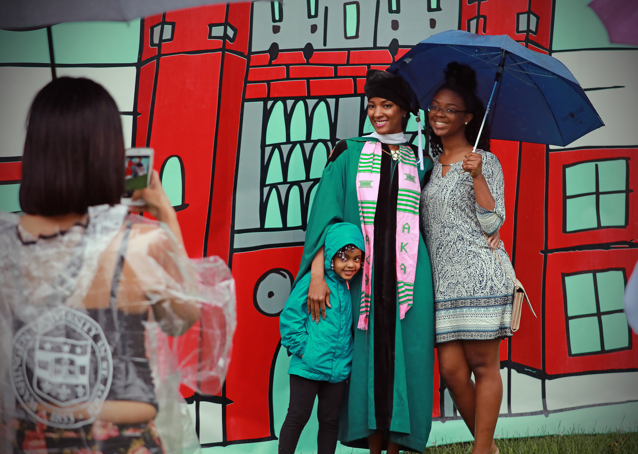 A college graduate, her parent, and young sibling stand in front of a backdrop of Brookings Hall at WashU