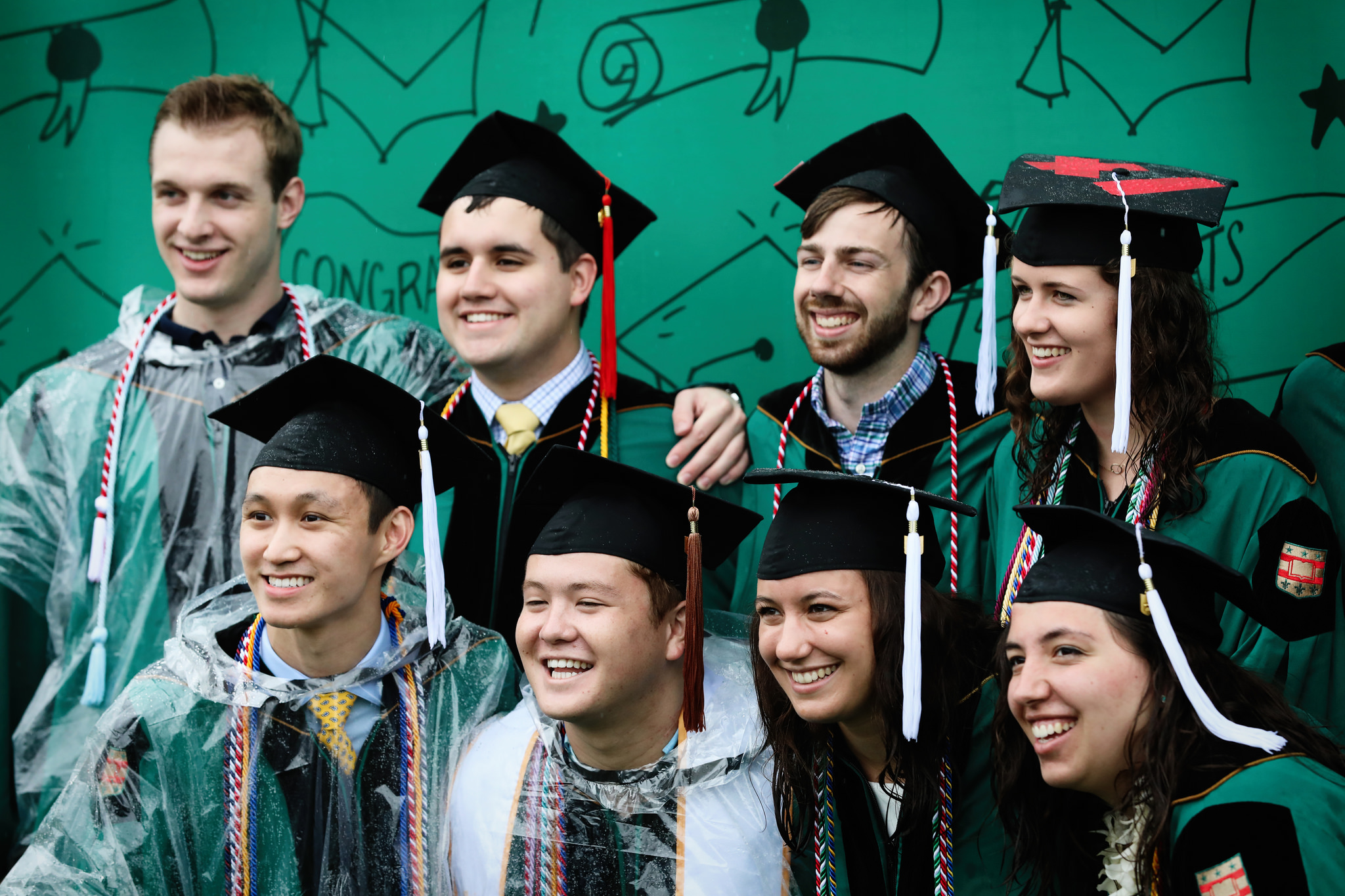 A group of WashU students in cap and gown pose for photos in front of a green illustrated backdrop