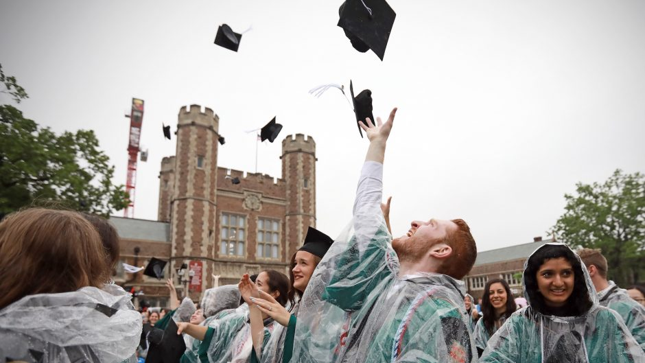 College graduates wearing rain ponchos toss their caps into the air at Commencement