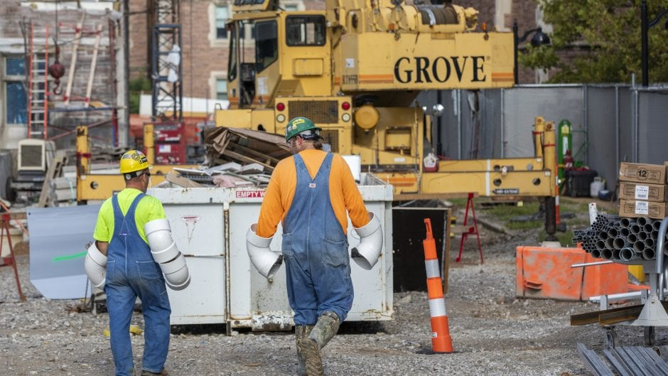 Two construction workers in overalls wear pvc pipes on their arms