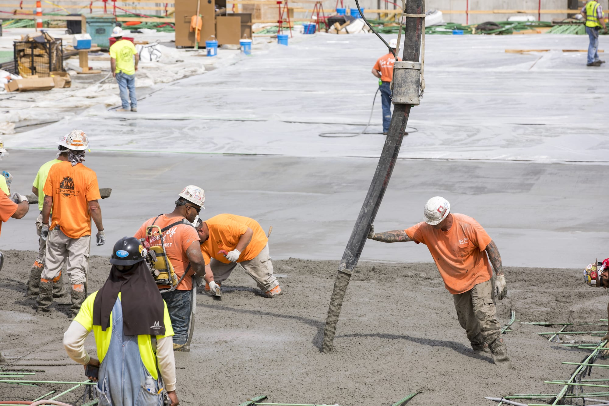 Constructoin workers in orange shirts pour concrete onto a massive surface.