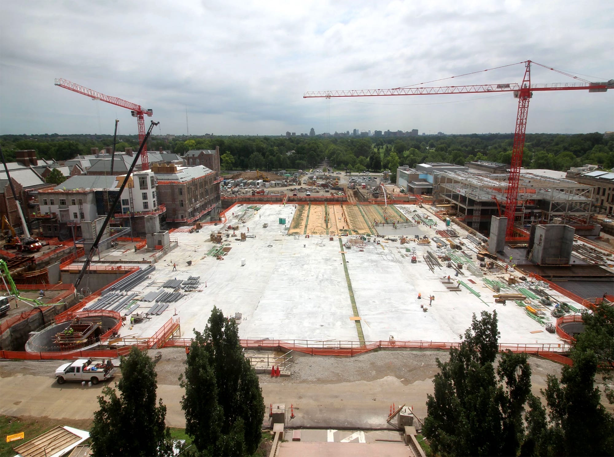 large expanse of concrete on a construction site with red cranes