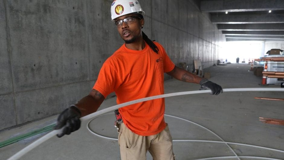 An African-American construction worker handles piping in the interior of a concrete structure.