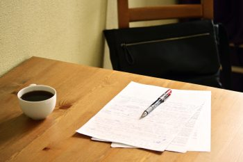 Desk with coffee and paper and pen.