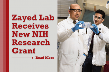 Picture of Mohamed Zayed, MD, MBA, in a white coat in a lab with a research trainee examining findings.