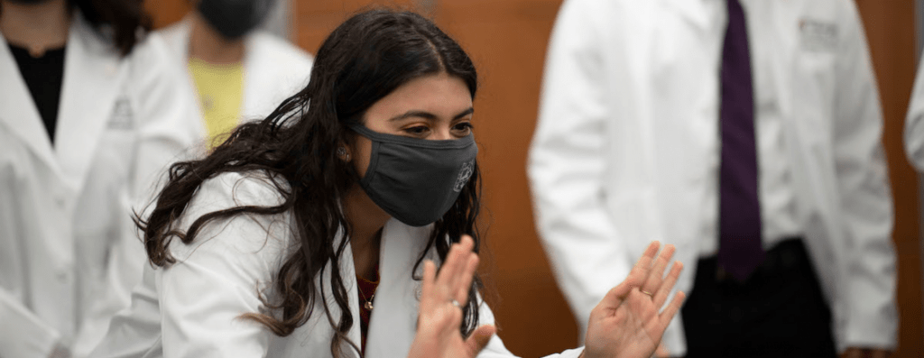 """First-year medical student Sneha Chaturvedi waves at her friends and family watching at home after they took part in a """"White Coat Reflection."""" Because of restrictions due to covid-19 coronavirus, they received their white coats and started their medical journey with a small group of students, their coach, and family and friends watching remotely on September 11, 2020. MATT MILLER/WASHINGTON UNIVERSITY SCHOOL OF MEDICINE"""