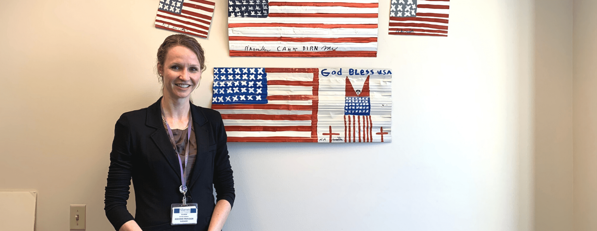Alison Snyder-Warwick, MD, smiles in front of patriotic art in the Plastic and Reconstructive Surgery Department.