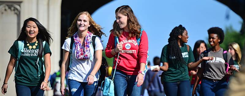 Students smiling as they walk away from the Brookings Hall archway on main campus