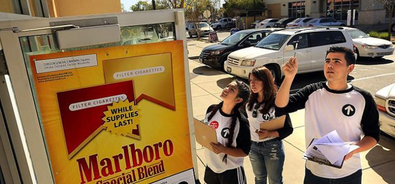 Group of evaluators looking at tobacco advertisement outside of gas station