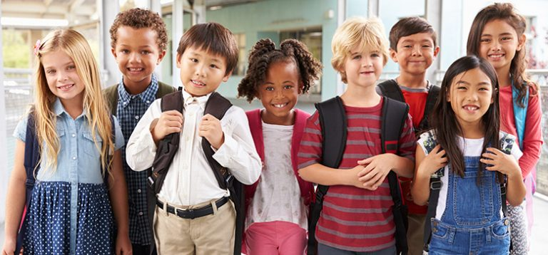 Diverse group of young children standing in front of school
