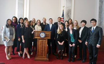 Students from the TPS course in DC gather around a podium