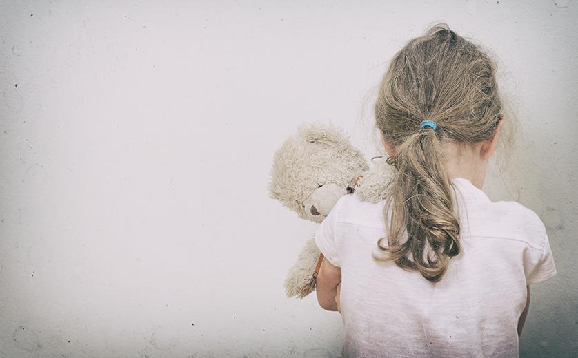 a little girls stands facing a wall holding a stuffed bunny