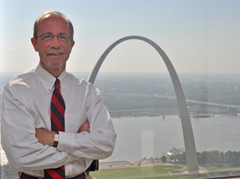 A photo of Tom Irwin in front of the arch