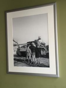 A photo displayed in the Caen Memorial Museum showing three French boys staring at a tank.