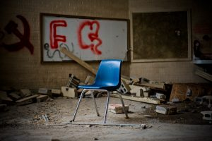 Lone school chair inside a old broken down school room with graffiti on the wall