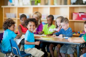 A diverse group of young students in a classroom together working at a table