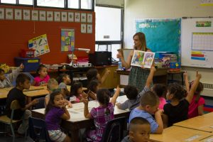 White female teacher leading class instruction for a diverse group of non-white students