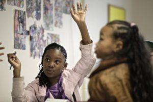 Black girls raising hands in classroom