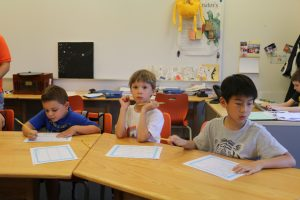 Young boys working on math worksheet in class