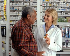 This is a picture of a man consulting his pharmacist. The pharmacist is holding a pill bottle and looks like she is explaining something to the man