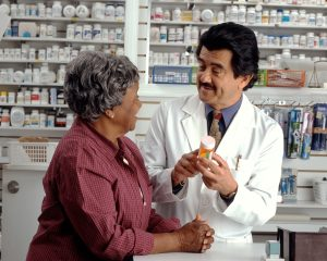This is a picture of a woman consulting with a pharmacist. The pharmacist is holding a pill bottle and is talking to the woman.